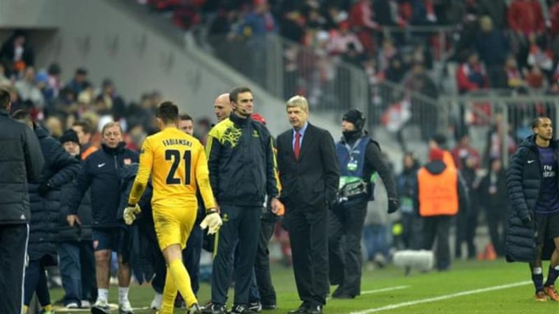 Arsenal coach Arsene Wenger (C) looks dejected after coming close to the quarter-finals [AFP]
