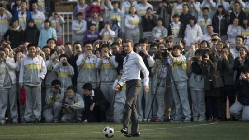 Style it like Beckham: Suited English star plays with Chinese children at Beijing's No. 2 High School [AP]