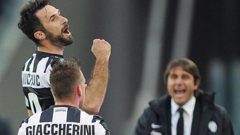 Montenegrin forward Mirko Vucinic (up) celebrates his goal with head coach Antonio Conte (R) [EPA]