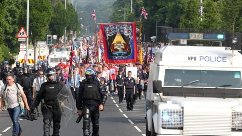 Police in riot gear escorted Orange Order marchers through the Catholic Ardoyne district of north Belfast [AFP]