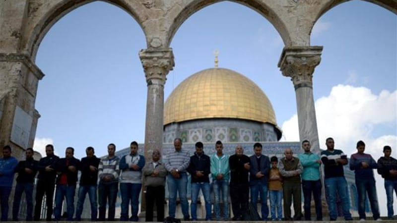Palestinians pray in front of Dome of the Rock in the Al-Aqsa Mosque compound [Getty Images]