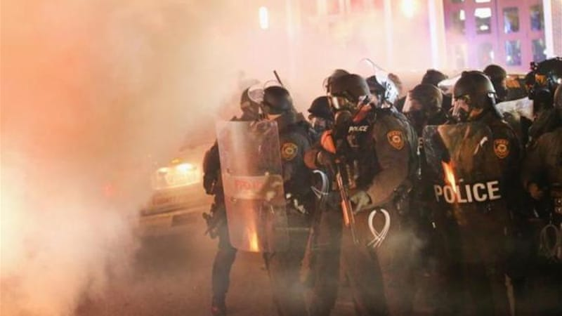 Police guard the Ferguson police department as rioting erupts [Getty Images]
