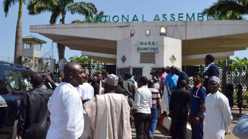Nigerian parliament members gather at the national assembly gate closed by security forces in Abuja on November 20, 2014. [AFP]