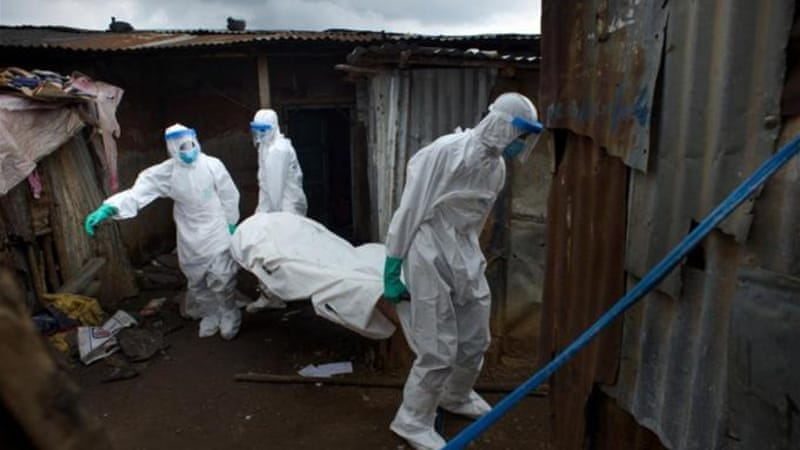 Members of a burial team remove the body of a 30-year-old man in Freetown, Sierra Leone [Getty Images]