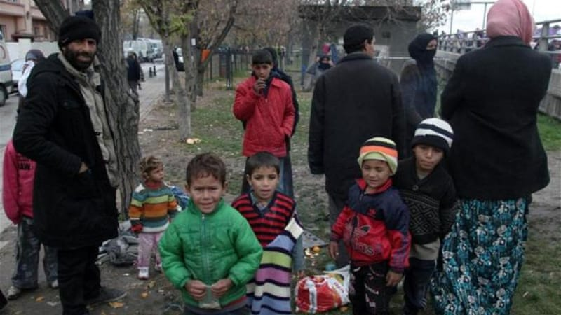 Syrian refugees who live in the streets stand in a public garden in central Ankara [AFP]