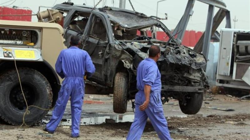 A destroyed vehicle is removed from the site of a car bomb explosion in Suweirah where 12 people died [AFP]