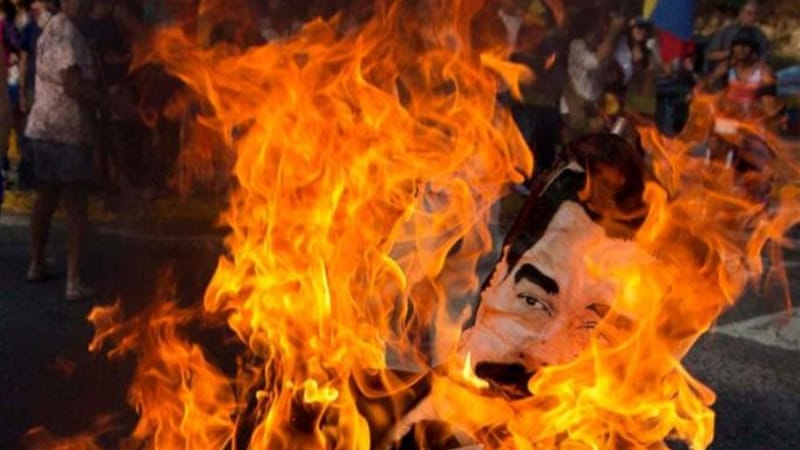 Protesters burned effigies of Maduro and government officials as part of a tradition 'burning of Judas' [AP]