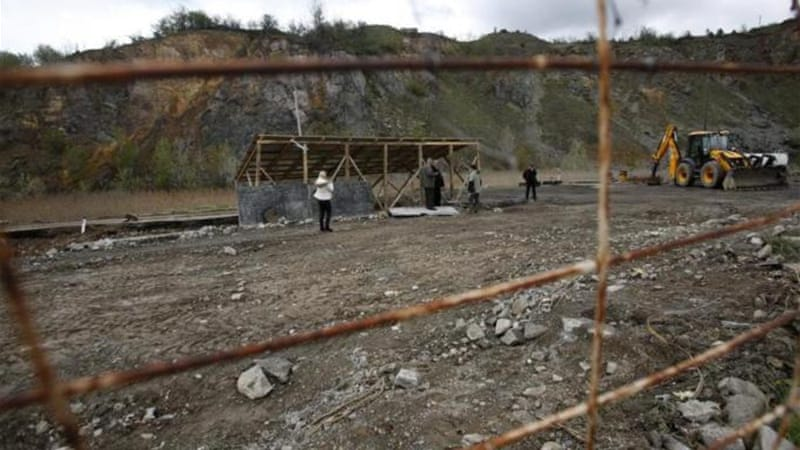 Experts inspect a mass grave site in the village of Rudnica, Serbia, which is believed to contain at least 250 bodies [AP]