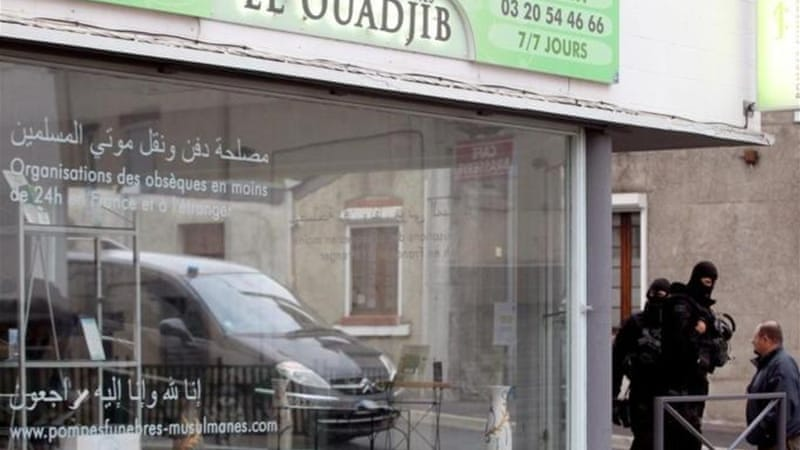 Members of the French National Police Intervention Groups in front of the Muslim funeral parlour 'El-Ouadjib' in northern France, during a raid as part of an investigation on a jihadist network leading to Syria [AFP]