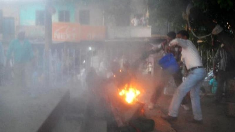 Indian bystanders attempt to douse the fire as a spectator set himself ablaze and embraced a local politician [AFP]