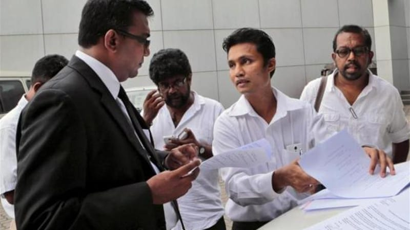 "Srilankamirror.com editor Kalum Shivantha, centre, said ""our stories were credible"" [AP]"