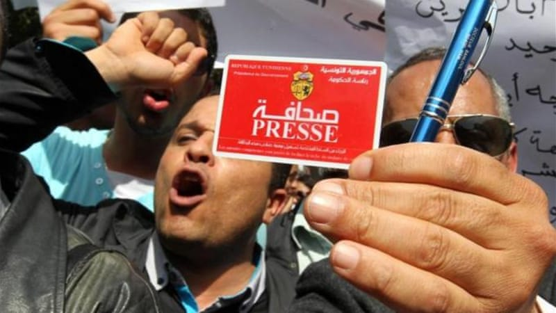 A Tunisian journalist displays his press card during a rally to mark World Press Freedom Day in Tunis [EPA]