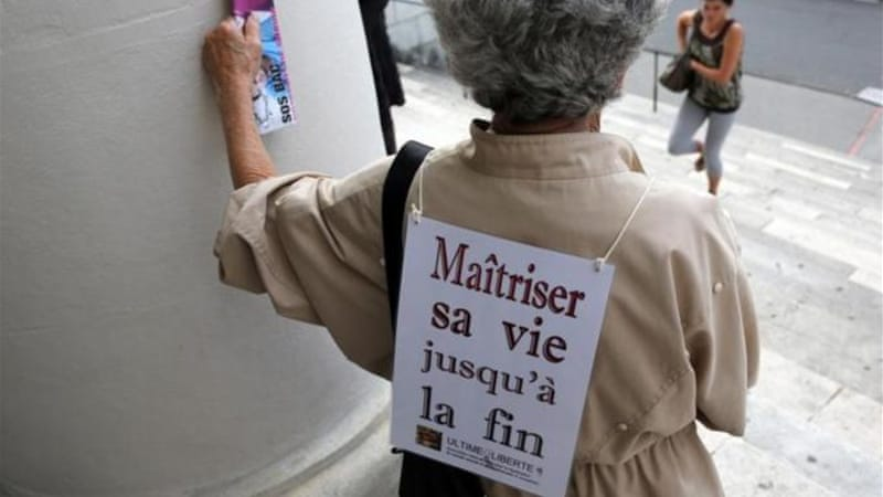 A woman carrying on her back a placard that reads 'Controlling one's life until the end' [AFP]
