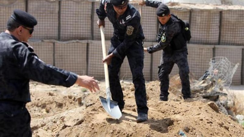 Policemen dig trenches in the Iraqi town of Taji, at Baghdad's entrance, as security forces bolster defences [AFP]