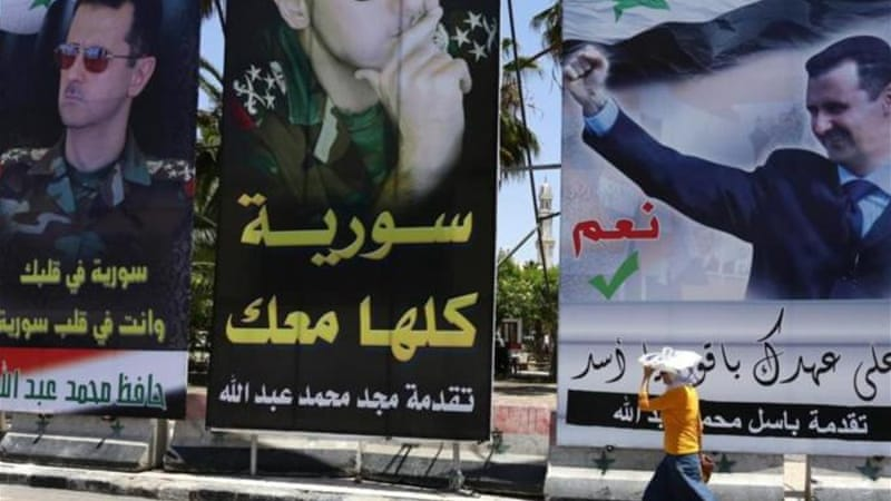 Campaign posters line the streets of Damascus ahead of Tuesday's poll [AFP]