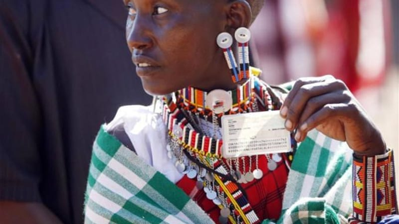 A Masai woman holds her ID card as she waits to vote [Reuters]
