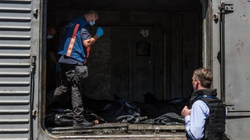 Each of the train wagons carrying the bodies was opened and examined by Dutch investigators [Reuters]
