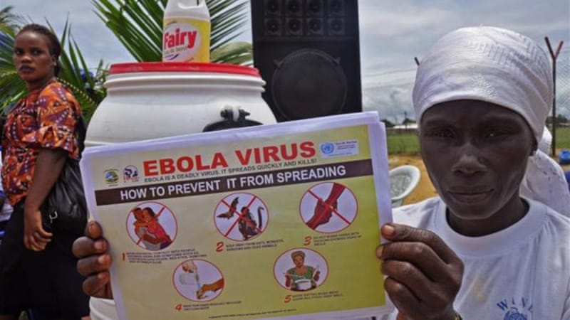 A Liberian woman holds up a pamphlet with guidance on how to prevent the Ebola virus from spreading, in the city of Monrovia, Liberia.  [AP]