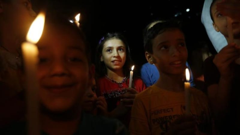 Palestinian children light candles next the rubble of a destroyed building in Gaza City on August 27, 2014 after a long-term truce took hold following a deal hailed by Israel and Hamas as 'victory' in