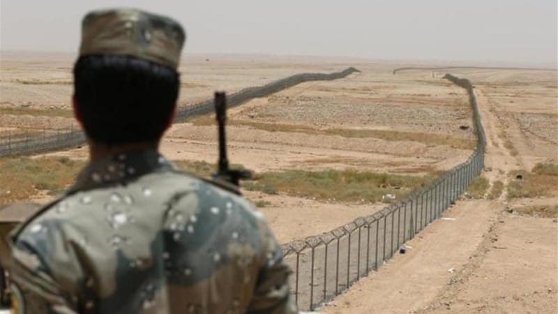 Saudi border guard stands next to a fence on Saudi Arabia's northern borderline with Iraq [Reuters]