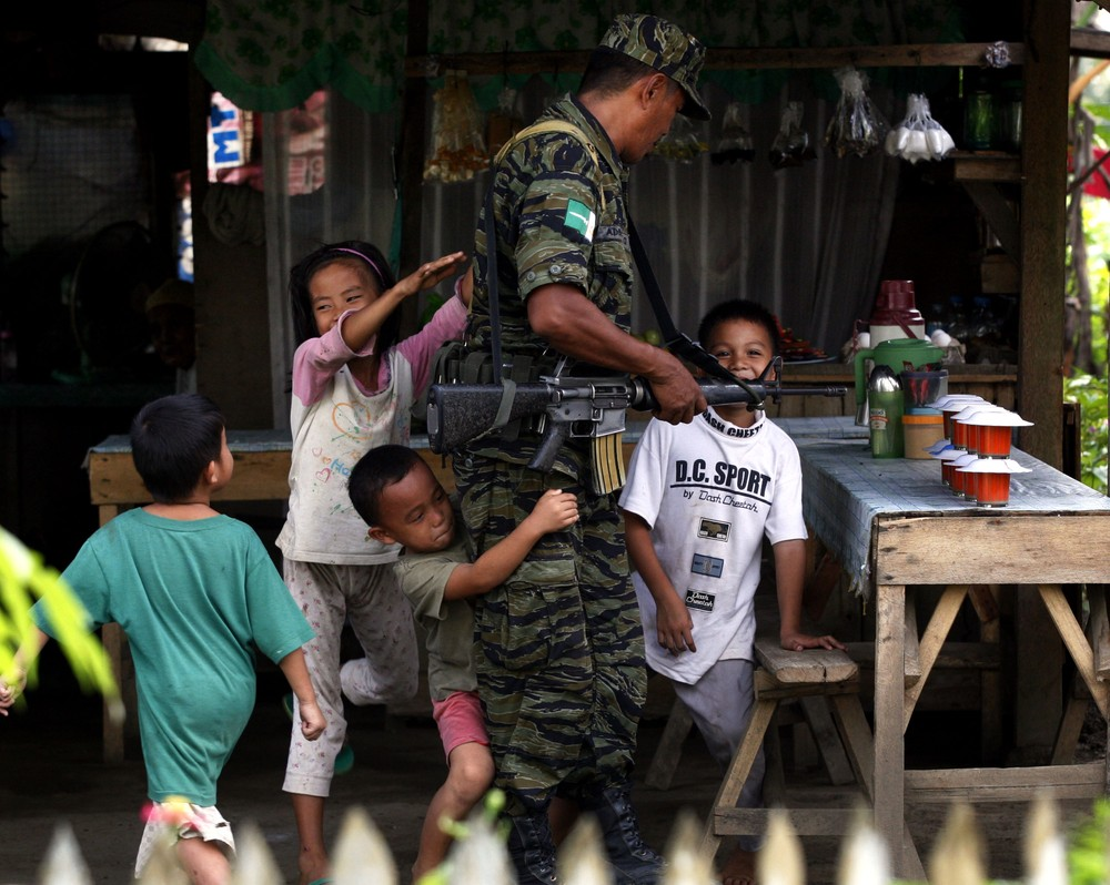 A group of children play with a Muslim rebel during a lull in fighting inside the rebel(***)s Camp Darapanan on Mindanao island in the southern Philippines.