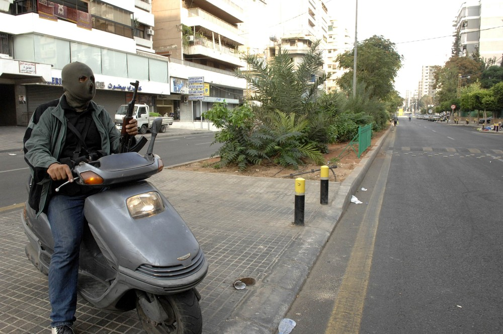 A  gunman  rides a motorcycle through the streets of Kaskas in Beirut , after a night of tension following the funeral of the anti-Syrian intelligence official Wissam al-Hassan