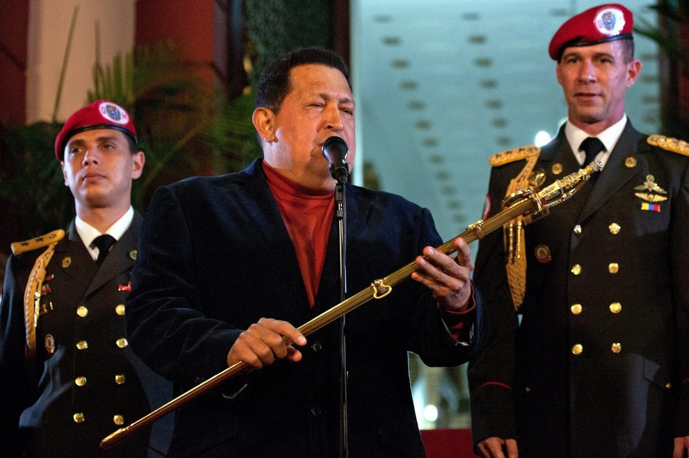 "Venezuelan President Hugo Chavez holds Simon Bolivar(***)s sword as he attends a press conference in Caracas. At the press conference held ahead of Sunday(***)s vote, he declared: ""I am sure that everything will be held in peace, and that all the political actors will respect the nation decision."""