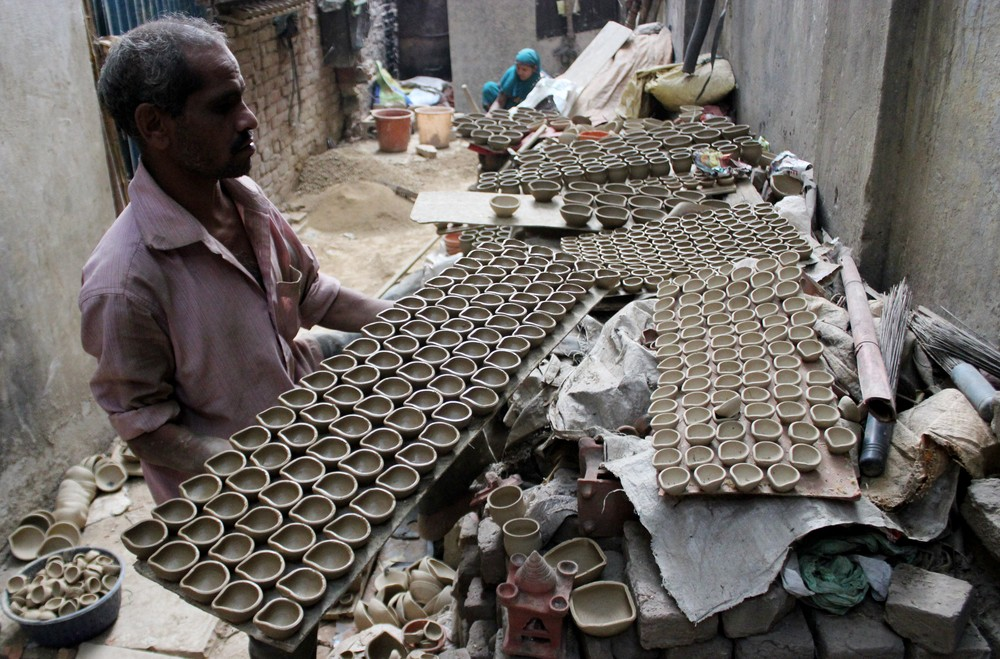 Potter Dev Karan Parjapati, 40, carries a tray of clay diyas before putting them in the kiln in Delhi.