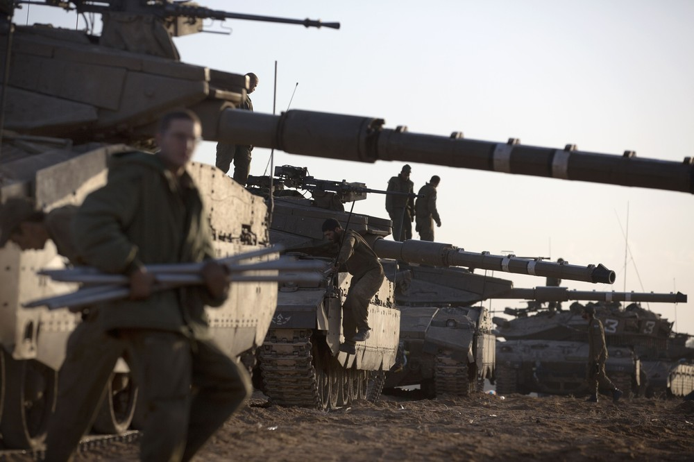 "Israeli soldiers prepare tanks at an Israeli army deployment area near the Israel-Gaza Strip border, in preparation for a ground operation in the Palestinian coastal enclave on November 18. Prime Minister Binyamin Netanyahu said that Israel is ready to ""significantly expand"" its operation against fighters in the Hamas-run Gaza Strip as it entered its fifth day."