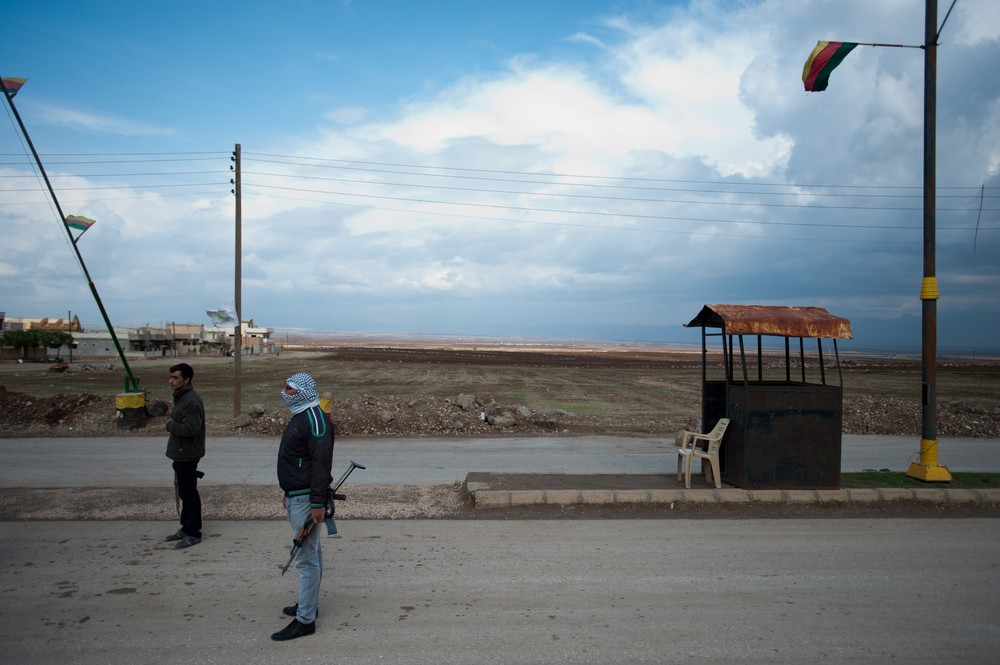 Members of a Kurdish local self-defence group man a checkpoint on the road to Derik, Syria.