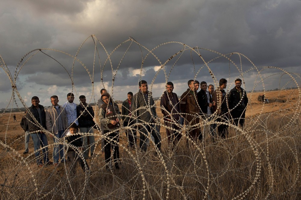 Palestinians gather along the Israeli-Gaza border fence in the Gaza Strip on November 23. The crowd, many returning to their farm land, were testing new agreements mediated by the Egyptians between Hamas and Israel that led to a ceasefire after eight days of cross-bordering fighting.
