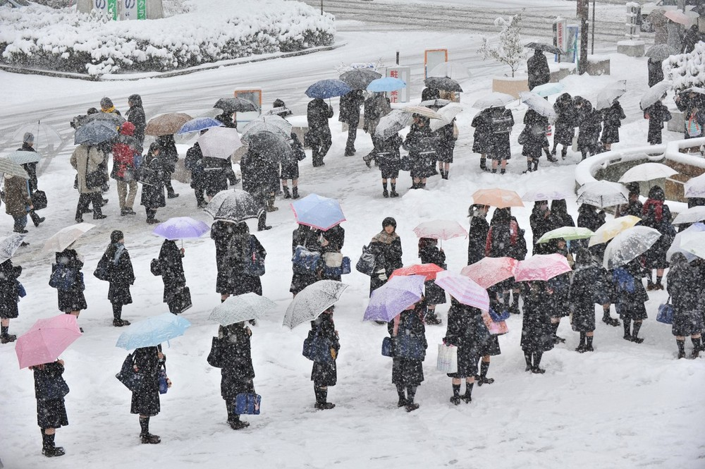 Students make lines on a bus terminal covered by snow to wait for transportation in Nagano City, Japan.