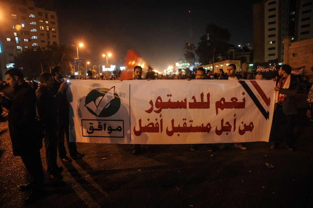 "Members of the Muslim Brotherhood march with a banner that reads, ""Yes to the constitution, for a better future"" in Nasr City, Cairo. Rival sides in Egypt are staging rallies a 