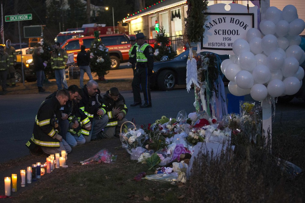 Firefighters pray in front of a memorial along the road to Sandy Hook Elementary School, on December 15. Investigators said they were assembling evidence to explain what drove 20-year-old gunman Adam Lanza to execute one of the worst mass shootings in US history.