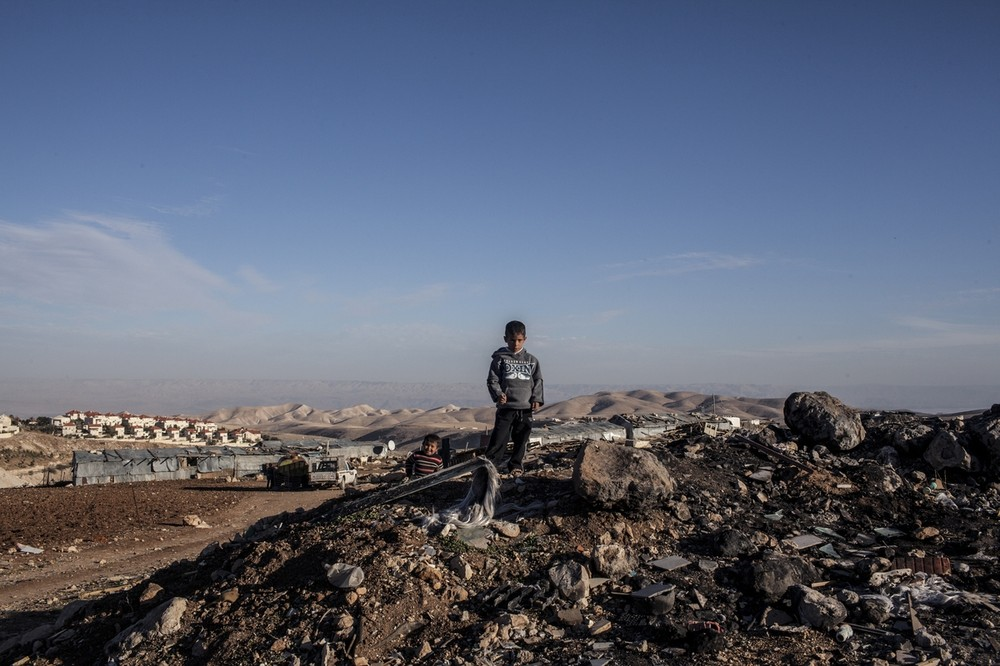 A young boy from Abu Nowar Bedouin community with Ma(***)aleh Adumim settlement in the background. Like Khan al-Ahmar, the community is part of a cluster of Bedouin communities living in or near the E1 corridor, which is slated for expansion. Already served with demolition orders, the 118-person community bides its time.