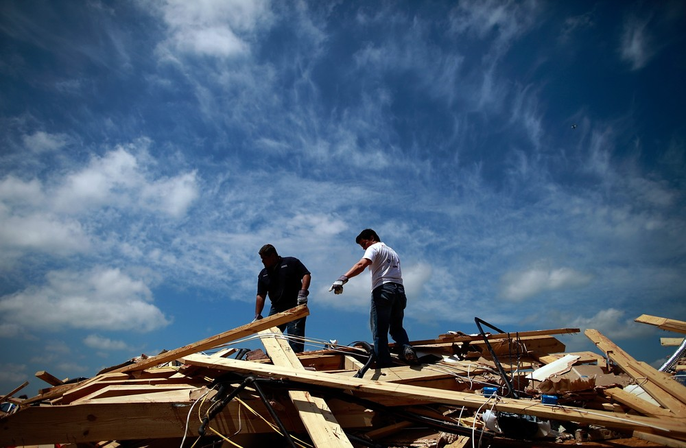 Volunteers help a friend search for personal belongings, following a tornado in Forney, Texas, after multiple twisters tore across the Dallas/Fort Worth area, causing extensive damage.