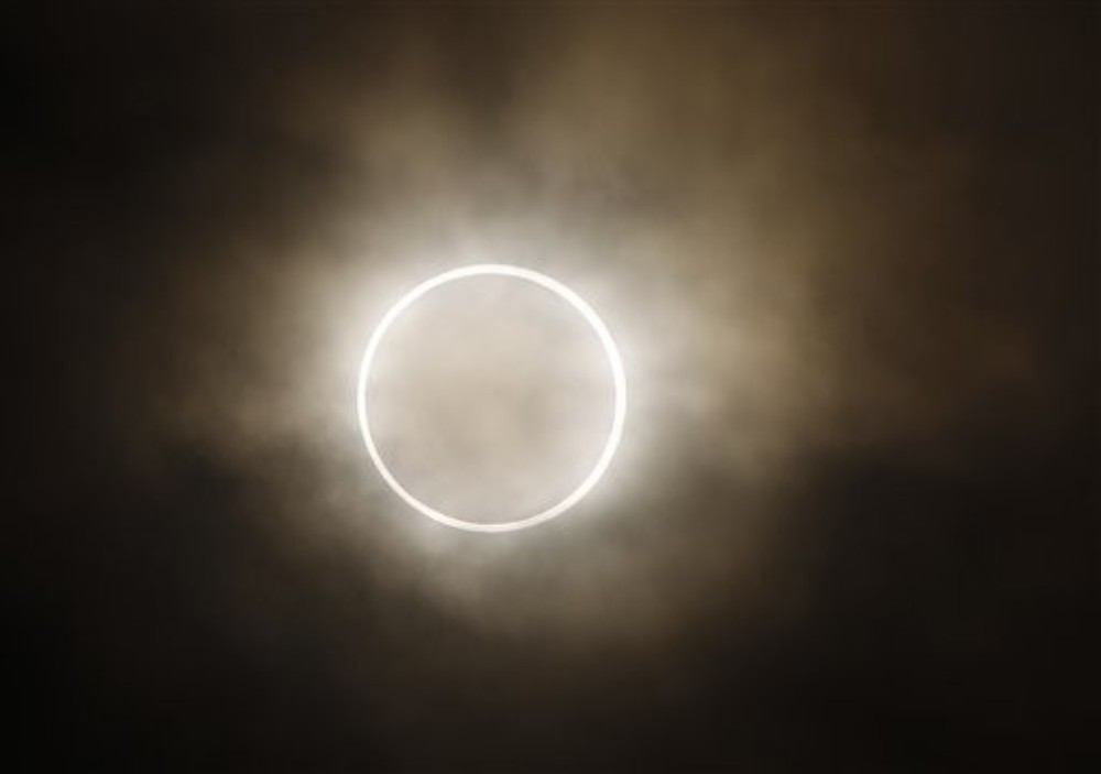 The moon slides across the sun, showing a blazing halo of light, during an annular eclipse viewed in Yokohama, near Tokyo, Japan.