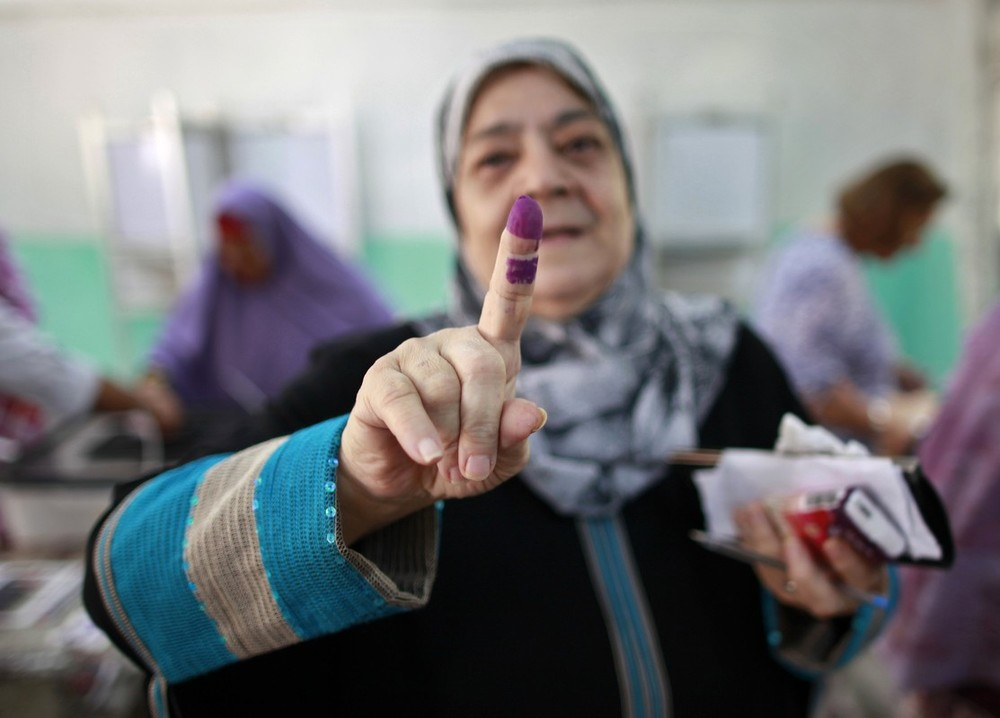 A woman shows her ink-stained finger at a polling station in Cairo in Egypt\(***)s presidential runoff election amid controversy 