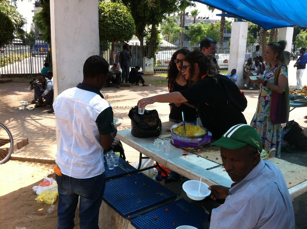 African migrants receive food from local charity workers offering social services in South Tel Aviv(***)s Levinsky Park.
