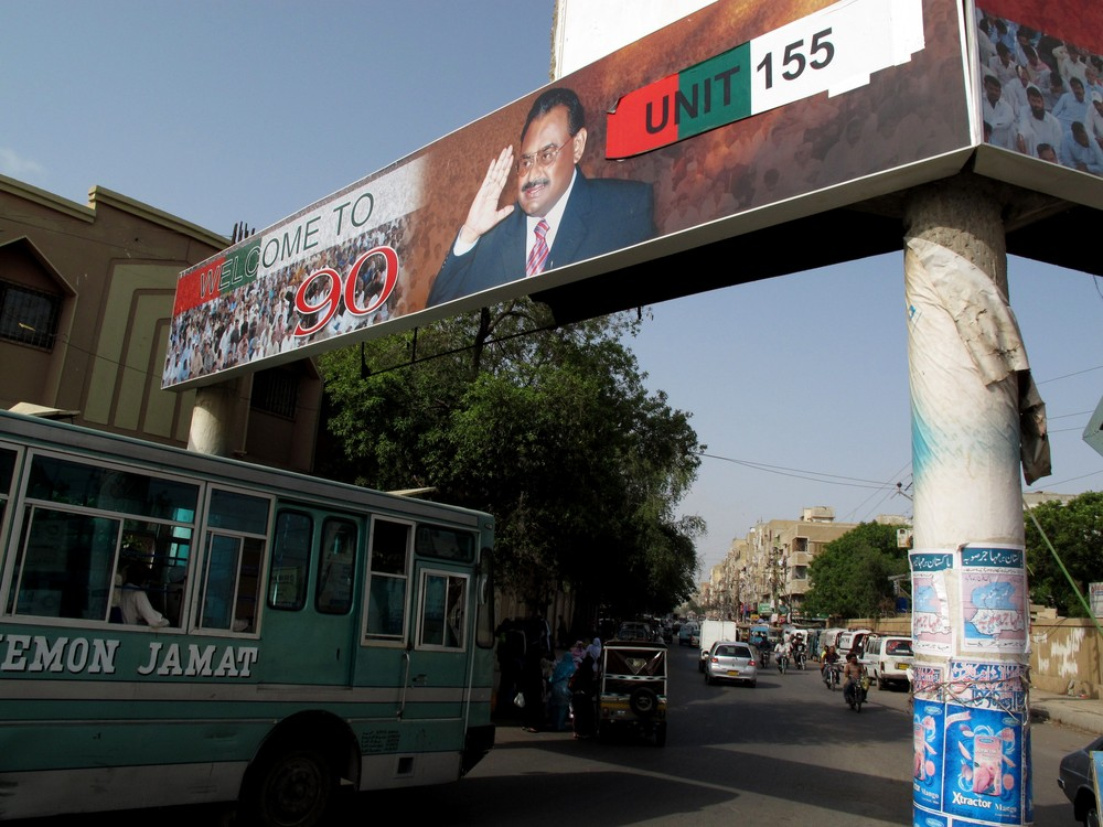 "The MQM is the dominant political party in the city. This sign shows Altaf Hussain, the party\(***)s founder and leader, welcoming people to the party\(***)s headquarters and Hussain\(***)s old residence, named ""Nine-Zero"" after the house\(***)s old telephone number."