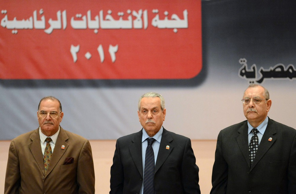 Farouq Sultan, center, head of the elections committee, gets ready to speak during the press conference where Mohamed Morsi is declared the official winner of Egypt(***)s presidential runoff.