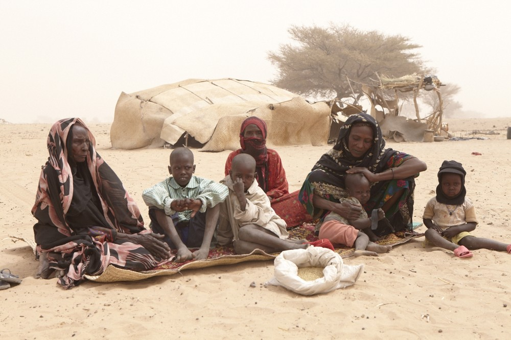 67-year-old Zeneba Louki sits on the left, with Etta Brahim, 36, outside her home in northern Chad with her children and sister, Ashta Hamid, in red. The whole family must survive for a week on the food in the white bag.