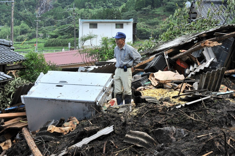 A Japanese worker stands among the debris of a landslide after torrential rainfall in Aso City, Kumamoto prefecture on July 17.
