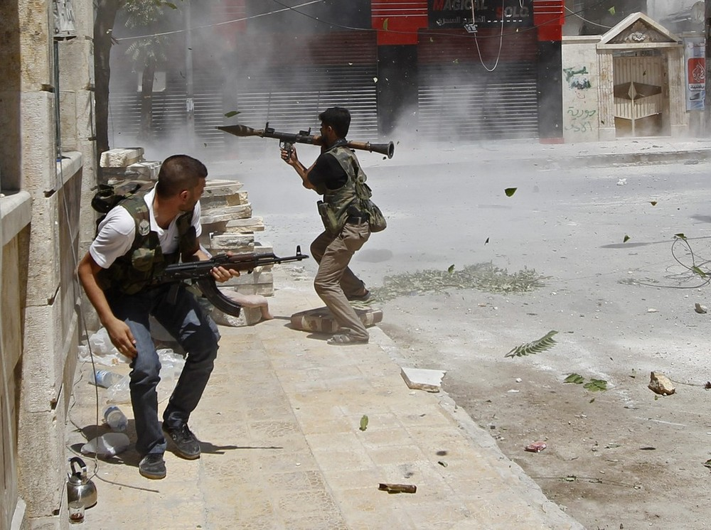 A Free Syrian Army fighter prepares to fire a rocket-propelled grenade as a Syrian Army tank shell hits a building across a street during heavy fighting in the Salaheddine neighbourhood of central Aleppo.