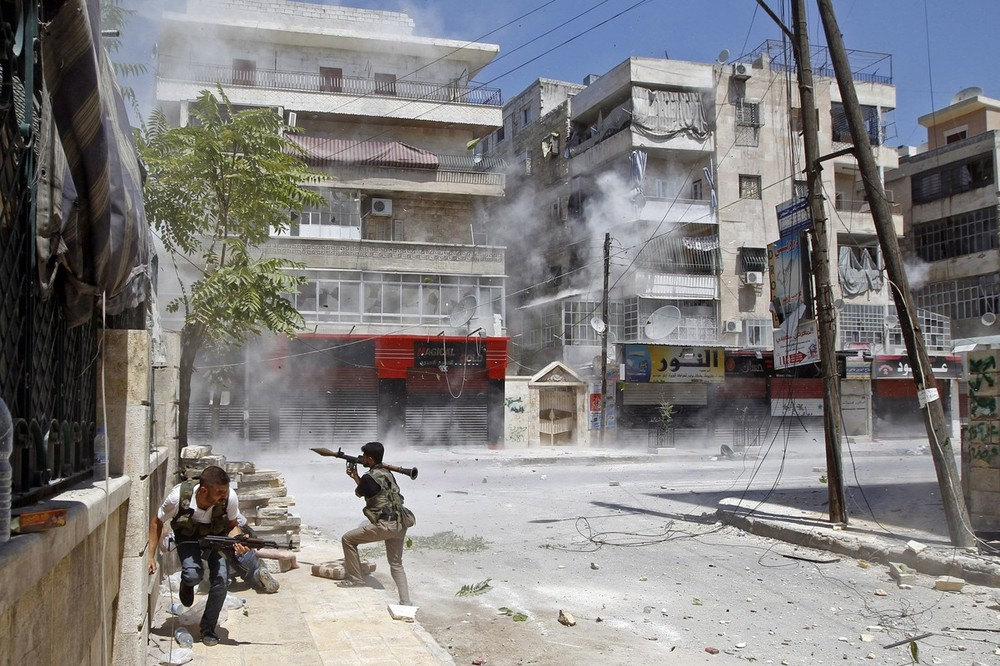 A Free Syrian Army fighter prepares to fire an RPG as a Syrian Army tank shell hits a building across a street during heavy fighting in the Salaheddine neighbourhood of central Aleppo, August 11.
