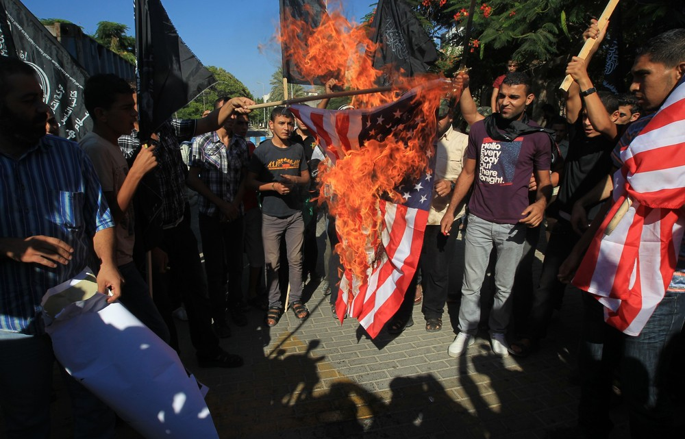 A film released on Youtube that is considered blasphemous has sparked violent protests and attacks on US diplomatic missions in several countries. Here a Palestinian man burns the US flag during demonstrations in Gaza City on September 12.