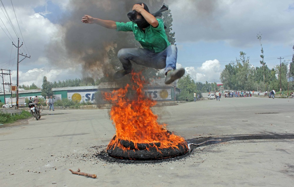 A protester jumps over a burning tyre. A photographer for news agency AFP said protesters threw stones and set fire to a police van.
