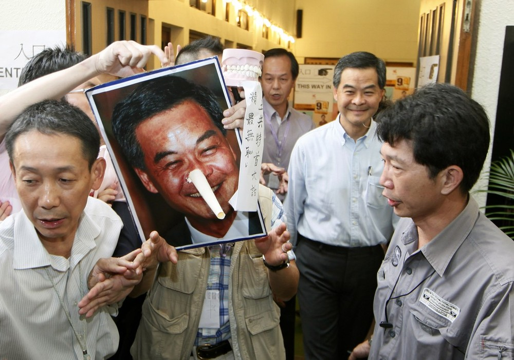 A protester holds a defaced portrait of Chief Executive Leung Chun-ying after Leung, right, voted at a polling station for the Legislative Council election in Hong Kong, on September 9.