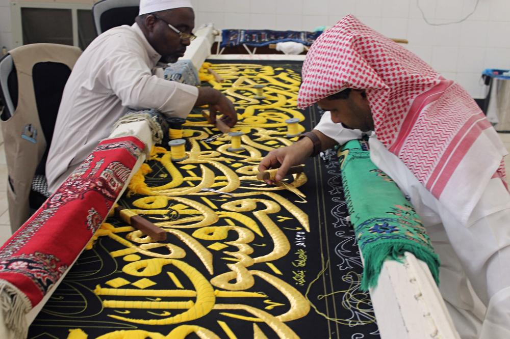<p>Workers put the final touches on the Kiswa - the black cloth that covers the Kaaba. The Kiswa is adorned with embroidered calligraphers.</p>