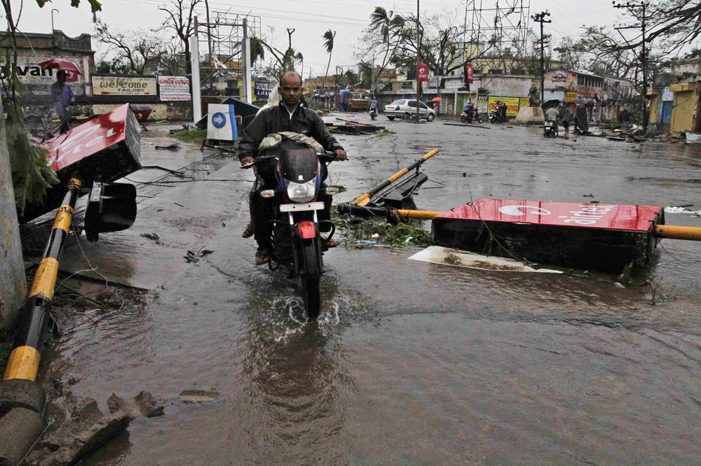 <p>A motorcyclist rides past fallen traffic signal poles during Cyclone Phailin at a road crossing in Berhampur, India.</p>